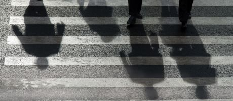 People's shadows cast on road crossing