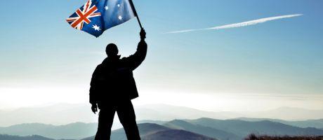 Silhouette of man waving Australian flag on hilltop