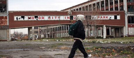 a person walks past the remains of the Packard Motor Car Company, which ceased production in the late 1950`s