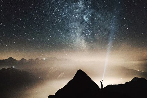 A man shining a torch up to the stars