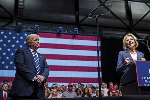 President-elect Donald Trump looks on as Betsy DeVos, his nominee for Secretary of Education, speaks at the DeltaPlex Arena, December 9, 2016 in Grand Rapids, Michigan.