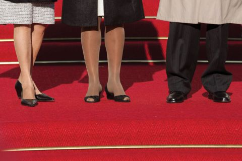 Women and man standing on red carpet