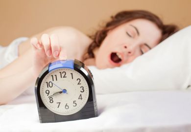 Yawning woman pressing alarm snooze button