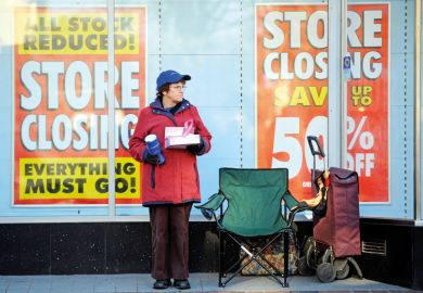 A charity collector standing outside a shop