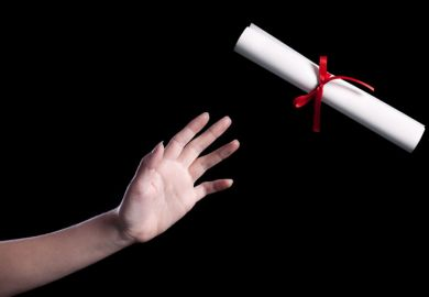 A hand reaching out to take a rolled up copy of a degree certificate