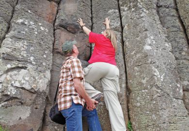 A man giving a women a leg up to climb a cliff