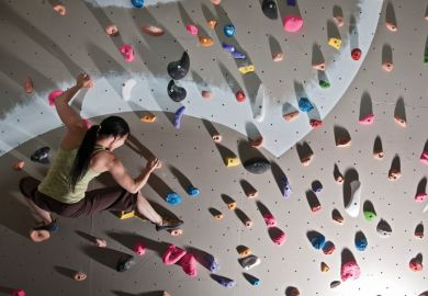 A woman scaling a climbing wall