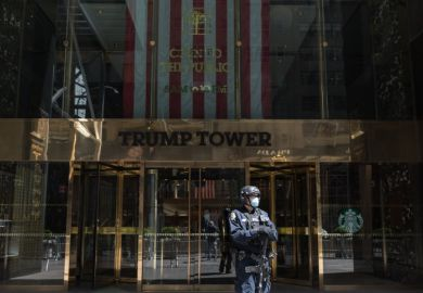 A counter-terrorism officer wearing a face mask stands at the entrance of Trump Tower