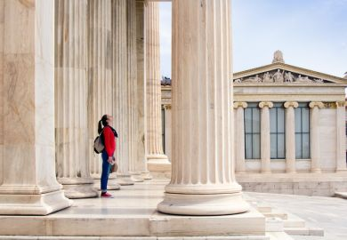 A girl looks up at the ceiling, under the columns of the Athenian Academy