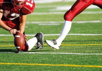 American football player preparing to kick ball