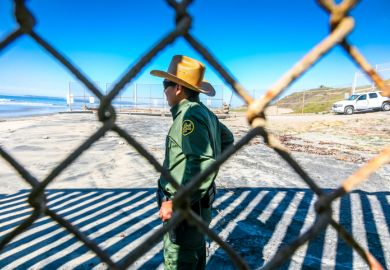 An agent of the US Border Patrol inspects the steel wall on the border between the United States and Mexico build on the Pacific coast of Tijuana
