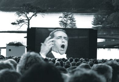 Audience watching opera singer on large screen
