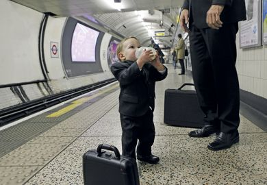 Man and little boy wearing suits standing on tube platform