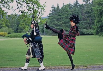 Woman behind man playing bagpipes