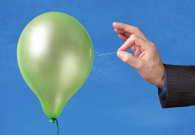 Hand bursting a balloon