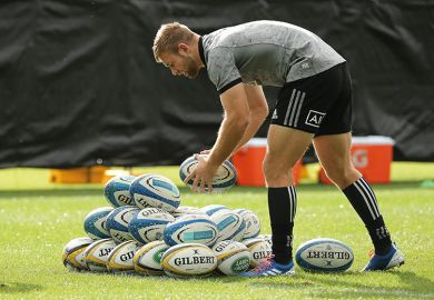 rugby player with pile of balls