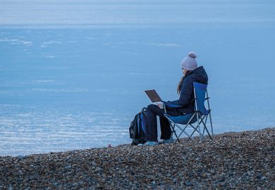 Working on laptop by sea in winter