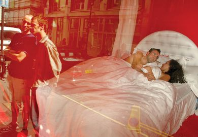 "Max Whatley and Meg Zakreta are watched by pedestrians as they lie in bed in a public artwork known as ""No Inhibition"" in the window of the Blink Gallery, August 29, 2002, in London, England, illustrating review of book On Getting Off: Sex and Philosophy"