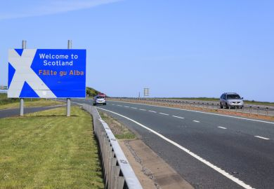 Berwick, UK - May 31, 2010 Cars on the A1 main road crossing the border between England and Scotland, passing the Welcome to Scotalnd sign with a stylised Saint Andrew's Cross scottish flag. Borders in the UK are open with no controls and free movement.