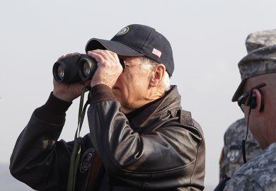 Joe Biden looks through binoculars toward North Korea