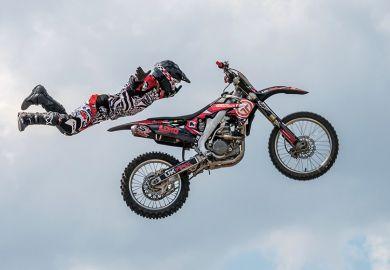 Motocross rider in mid-air illustrating university staff choosing to homeworking off campus