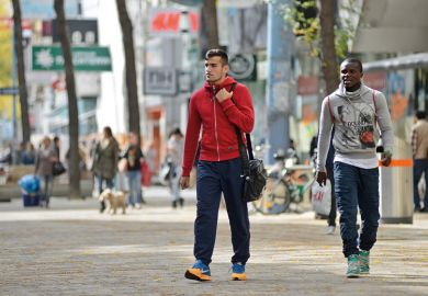 Black man and white man walking on high street