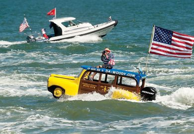 Man in boat shaped like a car with the American flag