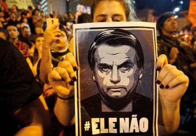 Woman holds poster of Jair Bolsonaro