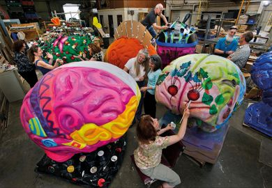 Artists painting brain sculptures