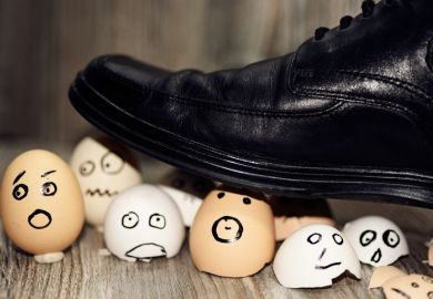Broken eggs under man's shoes