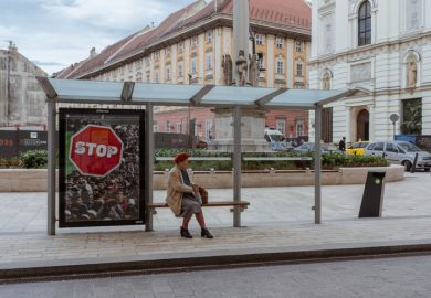 Budapest, Hungary - April 10, 2018 Elderly woman sitting in a bus stop with anti-immigration poster behind her