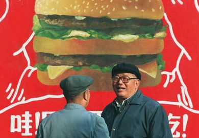 Two Chinese men in front of a billboard advertisement for a burger