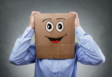 Businessman with smiley face cardboard box on his head