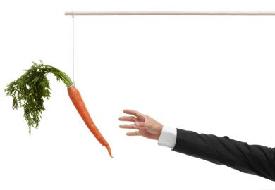 Businessperson's hand reaching for carrot on stick