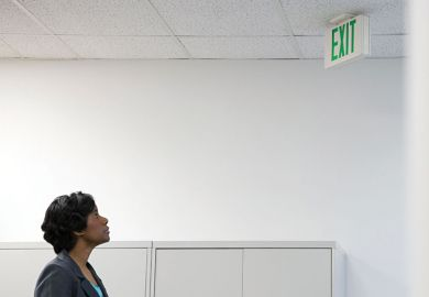 Businesswoman looking up at office 'Exit' sign