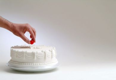 Cake with hand taking cherry on top
