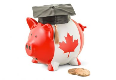 A Canadian piggy bank wearing a mortarboard