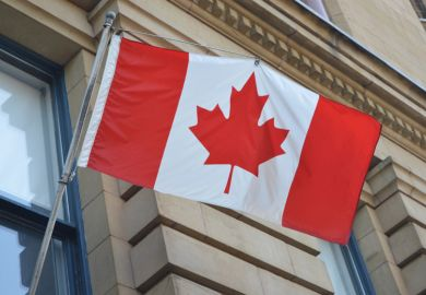 Canadian flag suspended outside building