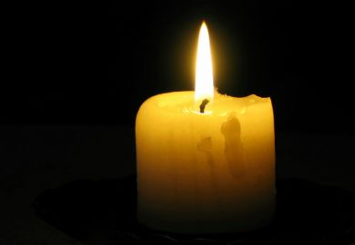 Candle burning in blacked-out room