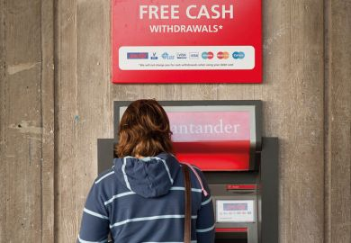 Student using ATM cash point machine