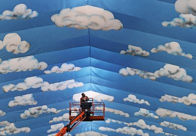 Cherrypicker against cloud mural