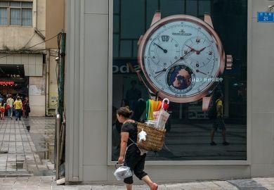 A local woman carries a bamboo basket, walking past a luxury watch shop at Jiefangbei CBD, Chongqing, 2015