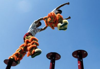 Chinese acrobatic performers jumping between poles