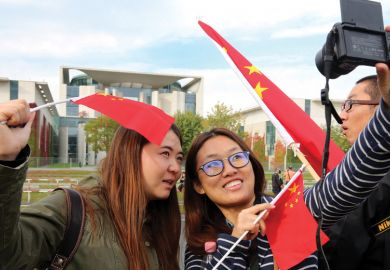 Two women take a selfie with Chinese flags