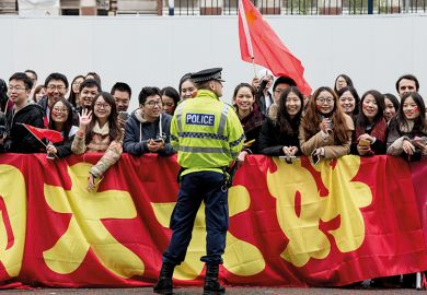Chinese students show support for Chinese President Xi Jinping as he arrives to tour the National Graphene Institute at Manchester University in 2015