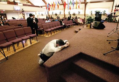 man prays in church