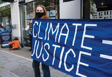 Woman holding climate justice protest banner