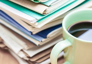 A stack of papers to mark and a cup of coffee