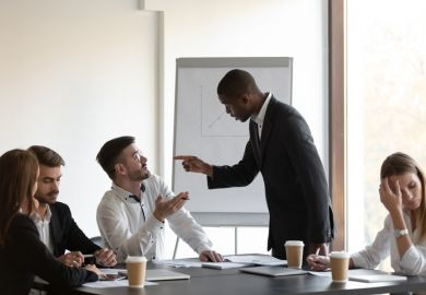 People gesticulate at each other in a business meeting, symbolising conflict within business schools