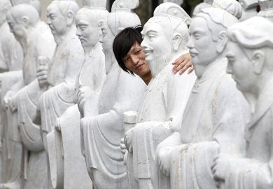 A visitor looks at the statues of Chinese sages, the 72 Disciples of Confucius, in the courtyard at the Koshi-byo, or Confucius Shrine, which also houses the Historical Museum of China, in Nagasaki, Japan
